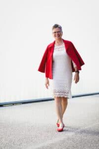 Cornelia Biesenthal mit cremefarbenem Kleid, roter Jacke und roten Schuhen
